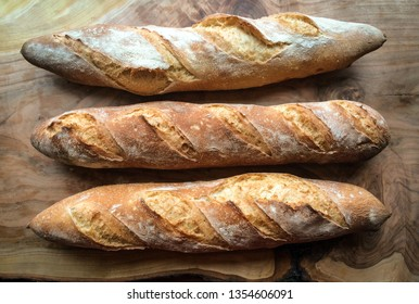 Three crunchy french baguettes on wood backgound