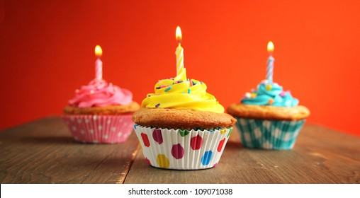 Three cupcake of different colors with birthday candle on a wooden table