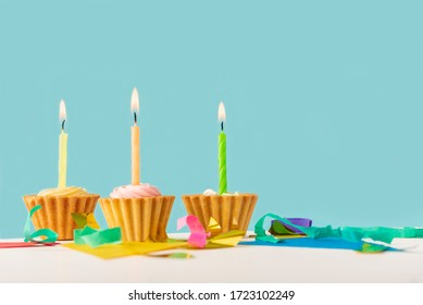 three cupcakes with candles on a white wooden surface