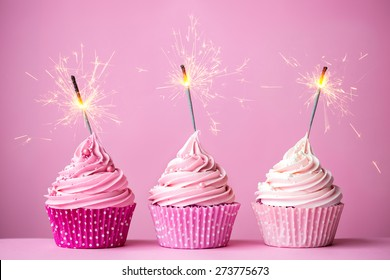 Three cupcakes with pink frosting and sparklers