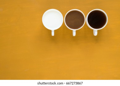 Three cups with coffee and milk on yellow background