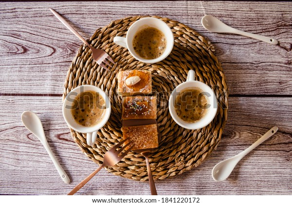 Three cups of coffee on rustic background, cakes on the table, seen from above