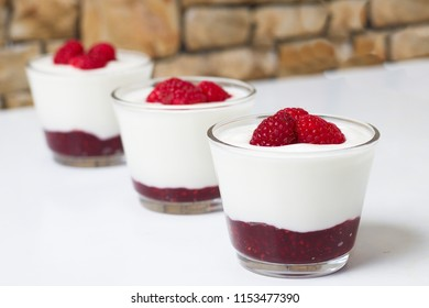 Three cups of fresh yogurt flavored by ripe raspberries and raspberry jam