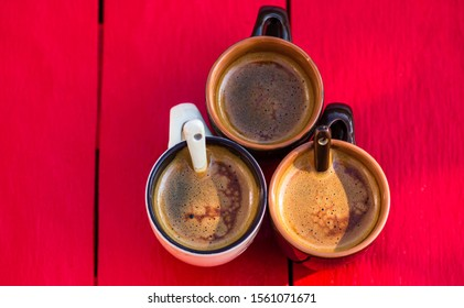 Three cups of homemade expresso coffee on red wooden board.