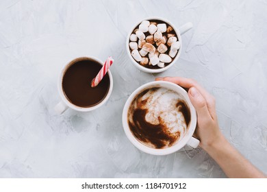 Three cups of vegan hot chocolate or cocoa with different toppings on grey