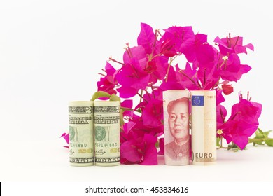 Three currencies, American dollars, China yuan, and European Union euro, in front of red bougainvillea reflect economic recovery hopes for fresh global growth.