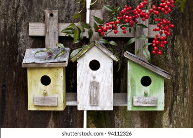 Three cute birdhouses with winter berries and old rustic wooden fence
