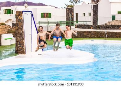 three cute boys jumping in the pool