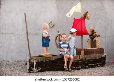 Three cute boys on a pirate ship as sailors on summer evening. Children have fun outdoors. Happy kids on holiday in the village. Home show with an vintage boat and a white chicken. Adventures going