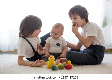 Three cute boys, siblings, brothers, playing with Easter eggs, eating chocolate bunnies at home, sunny living room