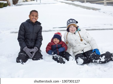 Three cute diverse boys playing together in the snow outdoors