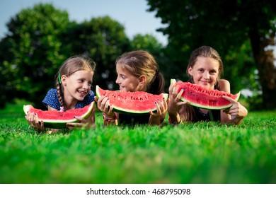 Three cute girls eating watermelon
