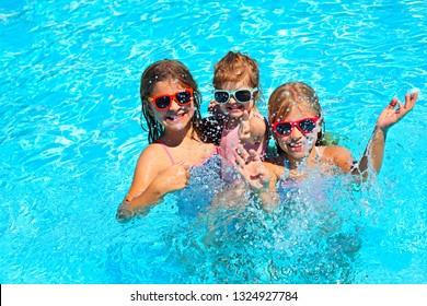Three cute girls playing in swimming pool. Summer vacation and travel concept