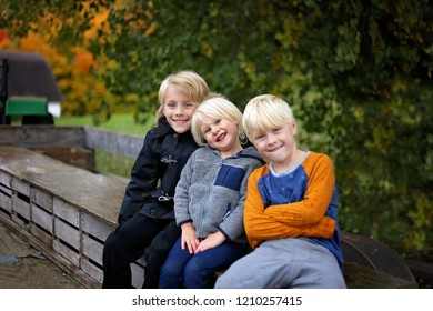 Three cute kids are smiling while they sit in the back of a tractor wagon at an apple orchard on a fall day.