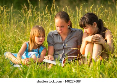 Three cute little girls reading book in natural environment together.