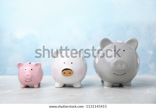 Three cute piggy banks on table against color background