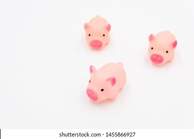 Three cute pink toy pigs are running forward on a white background