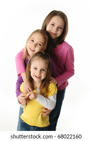 Three cute young sisters hugging each other, isolated on white