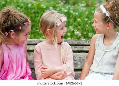 Three cute youngsters on wooden bench having fun.