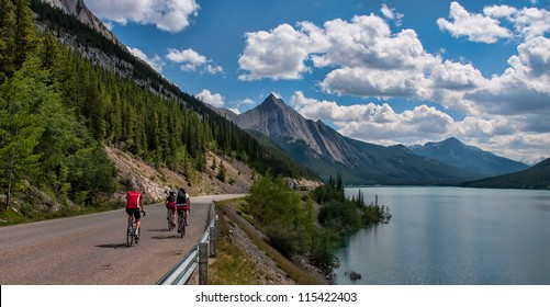 Three cyclists on a road in Jasper national park with a mountain peak in the distance.