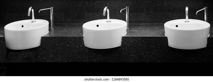 Three cylindrical white washbasins / sinks with soap dispensers on black granite countertop at public bathroom
