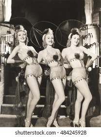Three dancers in fishnet costumes