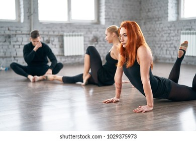 Three dancers warming up before a dance training.