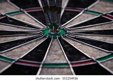 Three dart arrows hitting in the target center of dartboard illustrating the achievement of goals