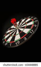 Three Darts in center of the target dartboard isolated on a black background