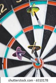 Three darts in the dartboard on the wall