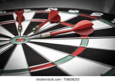 Three darts on the target center of dartboard.