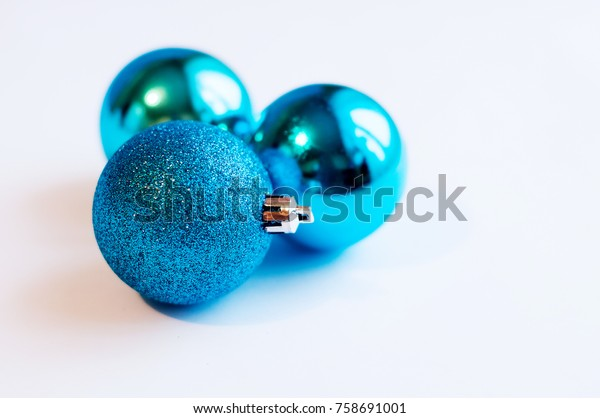 Three decoration blue balls on a white background with silver snowflakes around. New Year and Christmas decoration.