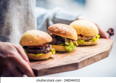 Three delicious hamburgers on wooden board. Toned image