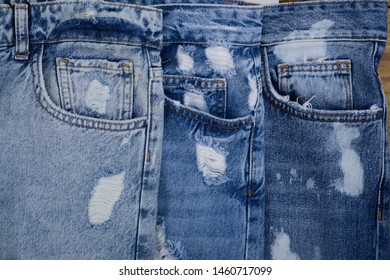Three Denim ripped Blue jeans lwith front pocket and seams close up view