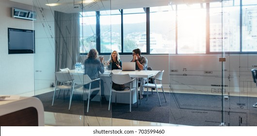 Three designers discussing about new project in meeting hall. Group of executives meeting in boardroom.
