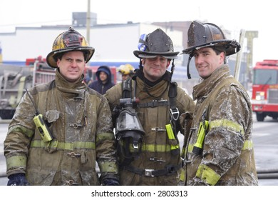 Three Detroit firemen posing at a fire