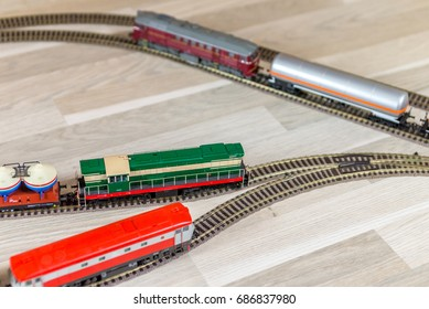 Three diesel model trains on wooden foor