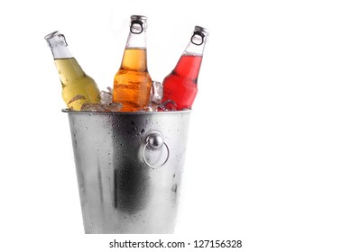 three different beer bottles in bucket of ice with condensation