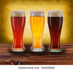 Three different beers on a rustic wood table.