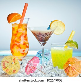 Three different boba tea cocktails with mango, orange, coffee and lime flavored. With paper umbrellas.