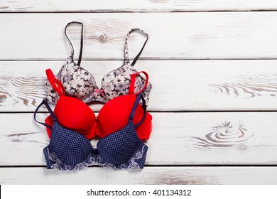 Three different bra on a wooden background.