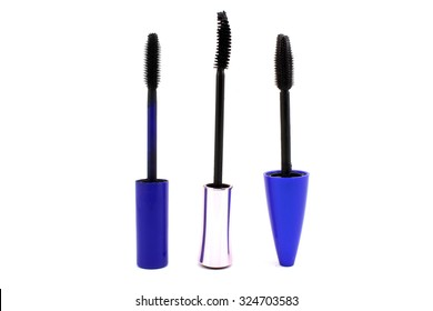 Three different brushes of mascara on a white background