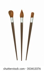 Three different brushes on white surface