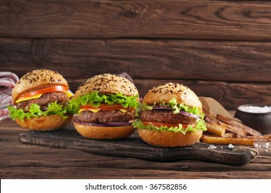 Three different burger on a wooden board on a dark rustic background