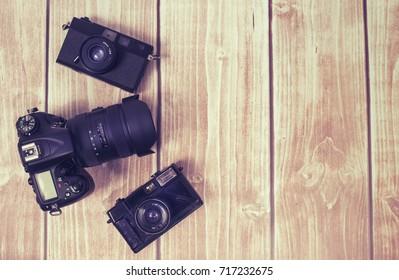 Three different cameras on brown wooden desktop
