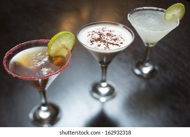 Three different cocktails on black table