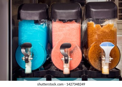 Three different color slush drink containers in a row, outdoors in summer.