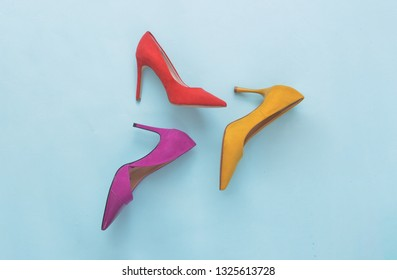 Three different colorful high heels on blue background