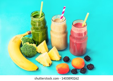 Three different colors cocktails in bottles with straw. Healthy smoothies, blue background.