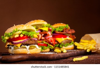 Three different delicious burgers with beef, tomato, cheese, cucumber, onion and lettuce on wooden table and brown background with copy space